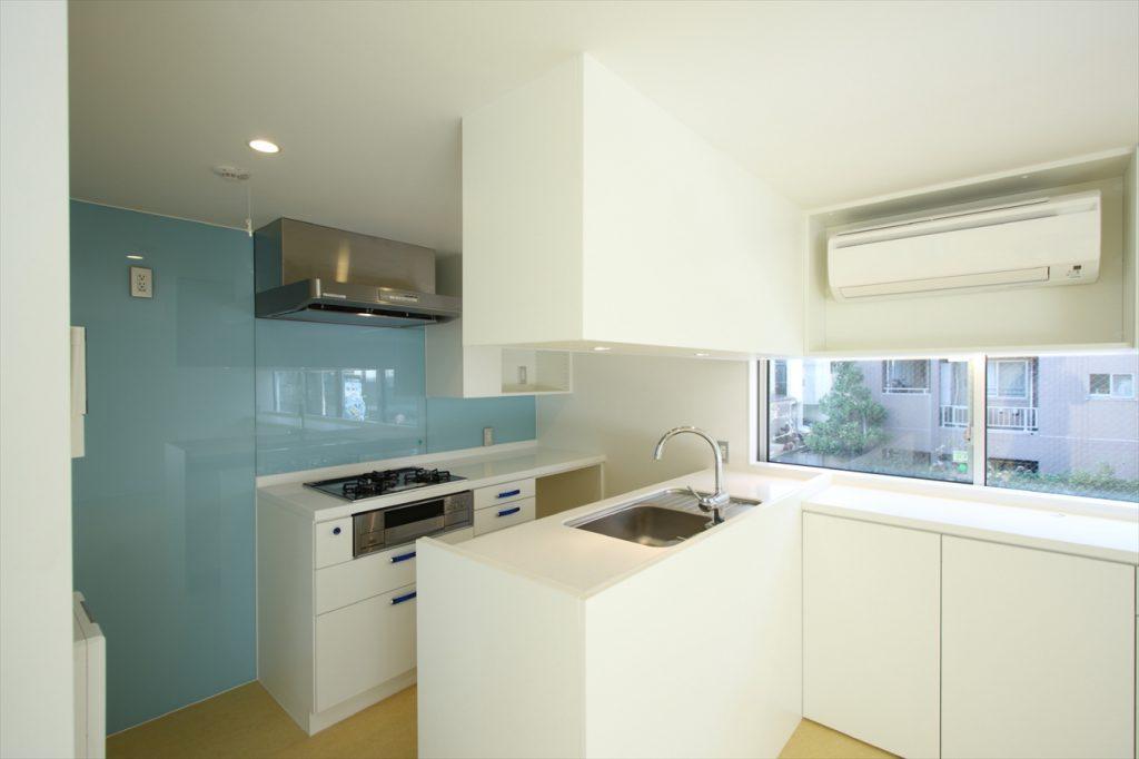 青いガラスパネルが貼られたキッチン