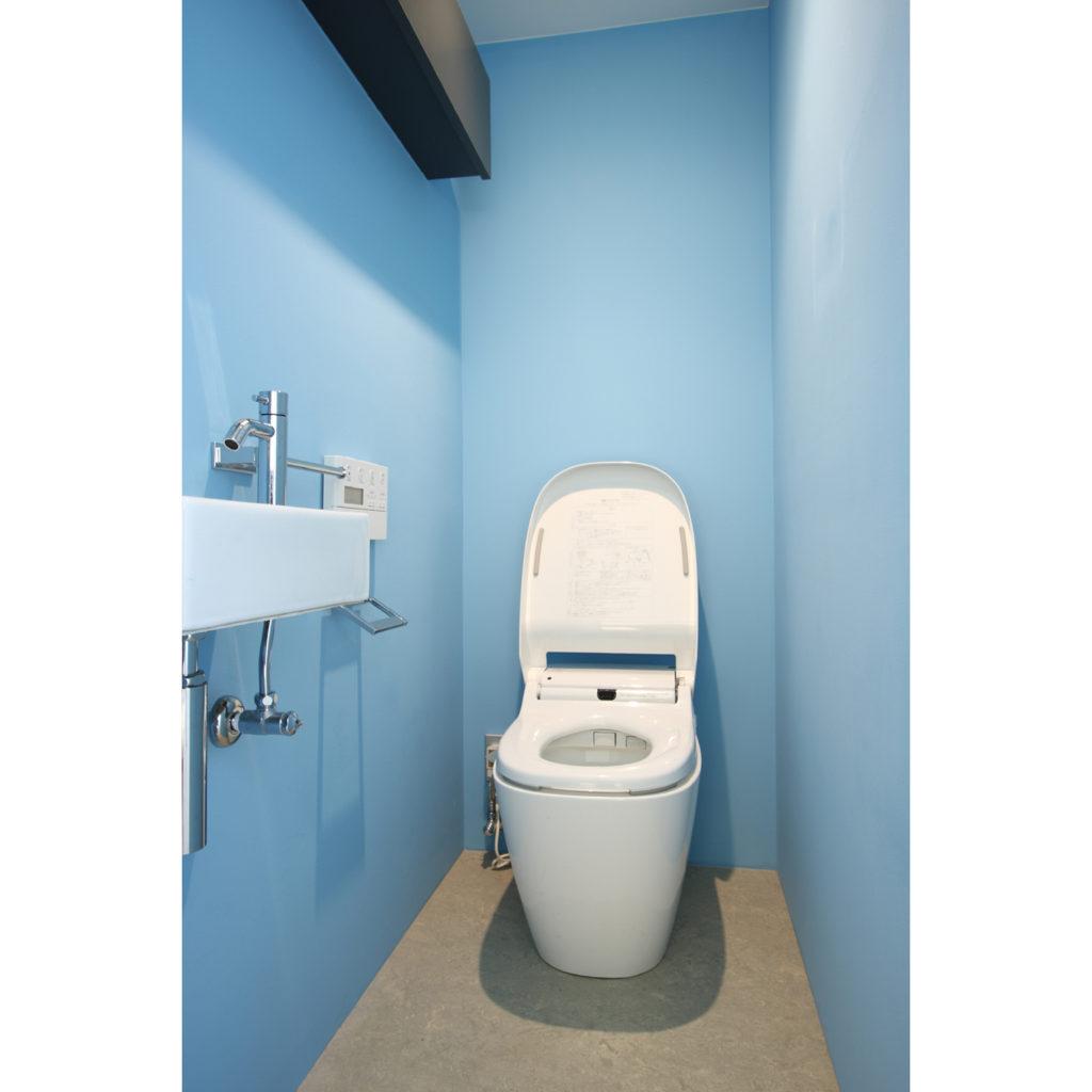 水色の壁で囲まれたトイレ