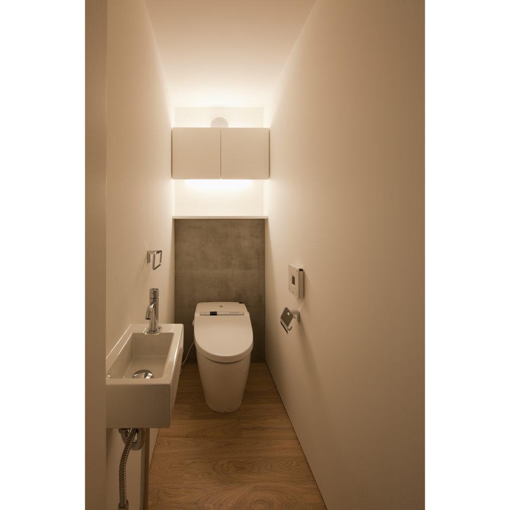 吊り戸棚に間接照明があるトイレ