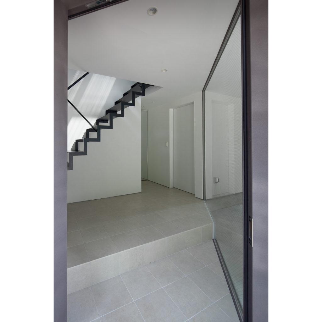 白いタイル張りの明るい玄関